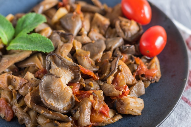 Fried oyster mushrooms with tomatoes on gray concrete background Premium Photo