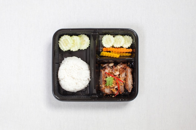 Жареную свинину с чесноком и перцем и рисом положить в черный пластиковый ящик, положить на белую скатерть, пищевой ящик, тайская еда. Premium Фотографии