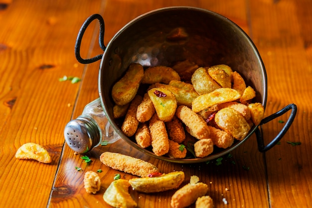 Fried potato wedges in the copper utensil on wooden table Free Photo