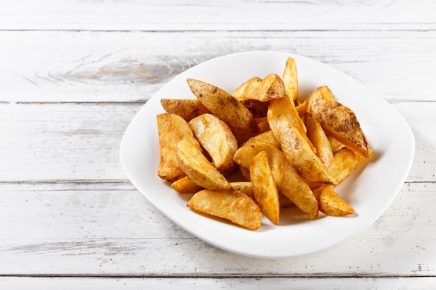 Premium Photo Fried Potatoes Slices Chips On Wooden Table