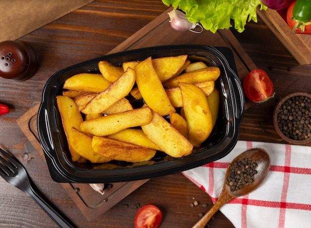 Fried potatoes with herbs takeaway in black container. Free Photo