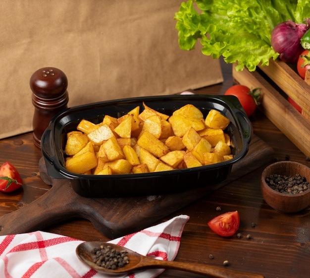 Fried potatoes with herbs takeaway in black container Free Photo
