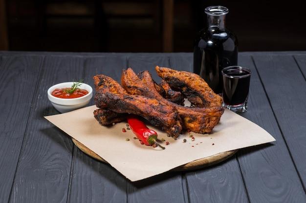 Жареные ребрышки с перцем и бутылка вина на черной деревянной поверхности Premium Фотографии