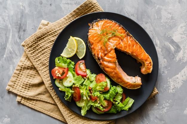 Fried salmon fish steak with vegetable salad Premium Photo