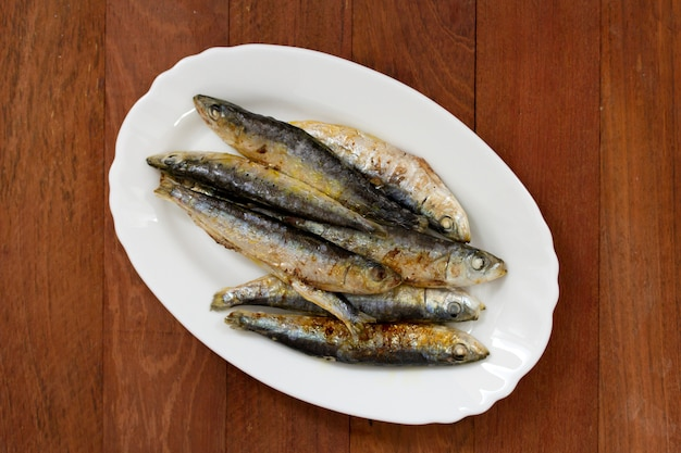 Fried sardines on white dish on brown wooden surface Premium Photo