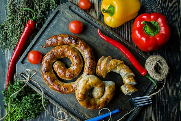 Fried sausage with herbs and spices, wooden. Premium Photo