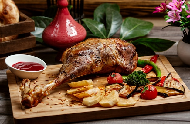 Fried sheep leg on wooden board Free Photo