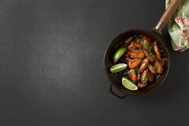 コリアンダーとライムをフライパンに入れて揚げたエビ。上面図。ビールスナック Premium写真