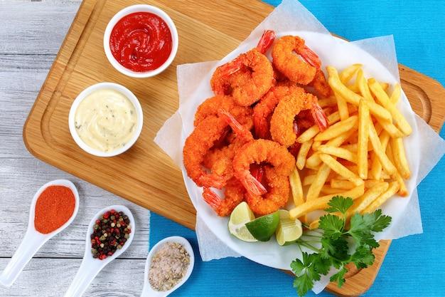 Жареные креветки, картофель фри и соусы Premium Фотографии