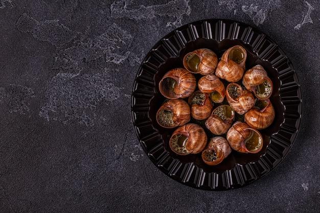 Жареные улитки с лимоном, багетом и петрушкой Premium Фотографии
