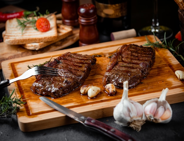 Fried steak pieces on a wooden board and garlic Free Photo