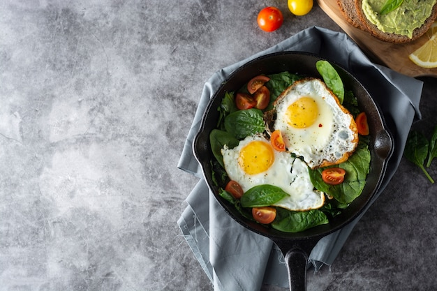 Fried sunny eggs with spinach, avocado toast and fresh tomatoes, healthy breakfast food, Premium Photo