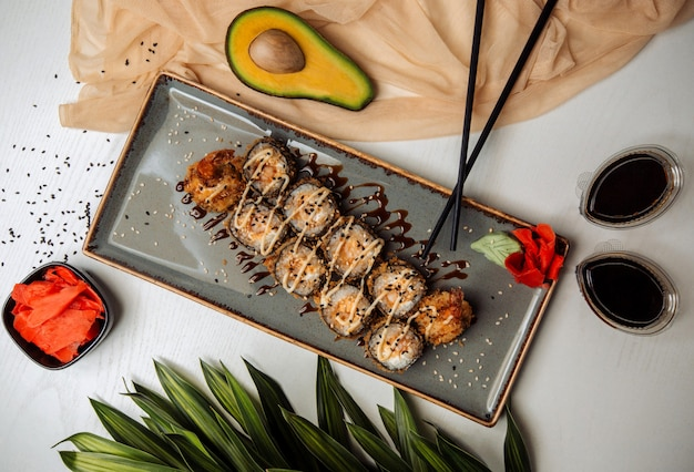 Fried sushi rolls garnished with sesame, teryaki sauce, served with wasabi and ginger Free Photo