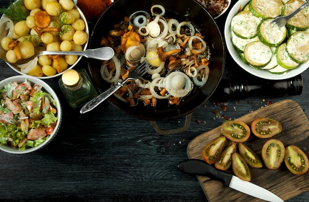Fried zucchini, young boiled potatoes with dill and fried chanterelle mushrooms with golden onions Premium Photo