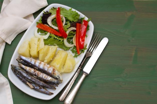 Friedでたジャガイモと緑の木の白い皿にサラダ揚げイワシ Premium写真
