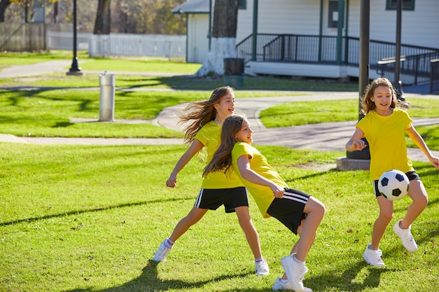 Friend girls teens playing football soccer in a park Premium Photo