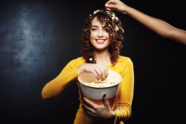 Подруга тушит попкорн на красивой женщине во время просмотра интересного фильма Бесплатные Фотографии