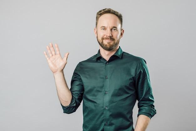 灰色の背景にこんにちはと言ってフレンドリーで幸せな若いひげを生やした男 Premium写真