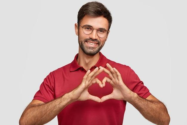 Дружелюбный, привлекательный бородатый самец жестикулирует, приятно улыбается, носит очки и красную футболку, выражает любовь Бесплатные Фотографии