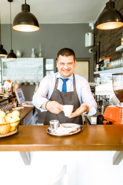 Friendly barman with coffee Free Photo