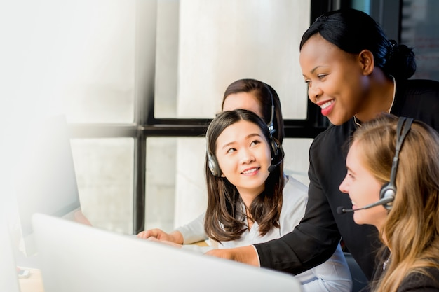 Friendly black businesswoman supervisor working with her team in call center Premium Photo