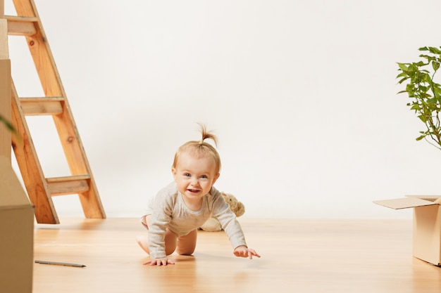Friendly blue eyed baby girl sitting on the floor indoors Free Photo
