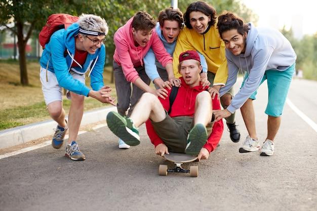 フレンドリーな男の子がスケートボードで仲間に乗る Premium写真