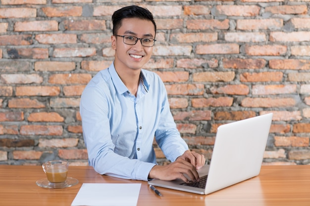 Friendly business man working on laptop at desk Free Photo