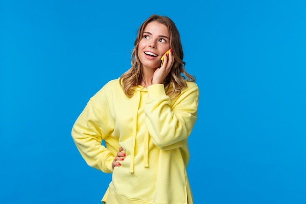 Friendly carefree good-looking blond woman talking on phone, holding mobile phone near ear and look up with pleased smile, thinking, making order or calling friend, on a blue wall Premium Photo