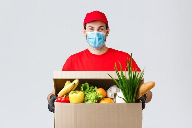フェイスマスクと手袋を着用したフレンドリーな宅配便で、コロナウイルス中にフードボックスをクライアントの家に配達し、非接触で配達 Premium写真