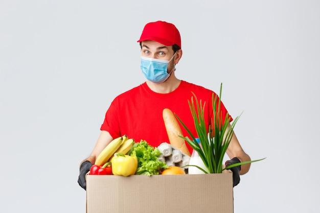 フェイスマスクと手袋をはめたフレンドリーな宅配便、赤い制服はオンラインで注文した顧客にフードボックスを持ち込み、非接触で配送します Premium写真