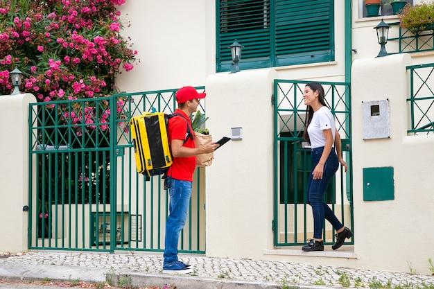등온 배낭이있는 친절한 택배가 고객 문에 음식을 배달합니다. 태블릿, 식료품가 게에서 종이 패키지와 여자 회의 배달 남자. 배송 또는 배달 서비스 개념 무료 사진