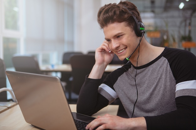 Friendly customer support operator with headset working at call center Premium Photo