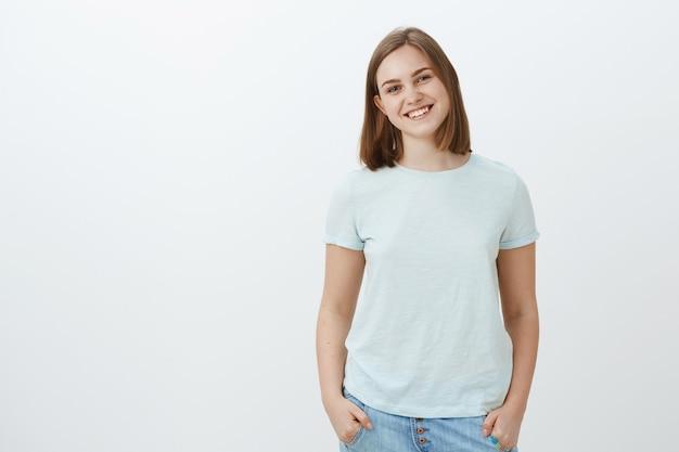 Дружелюбная милая белая девушка с короткой стрижкой и красивым ушком, радостно улыбаясь, держась за руки в карманах и глядя радостным развлеченным взглядом, позирует над белой стеной Бесплатные Фотографии