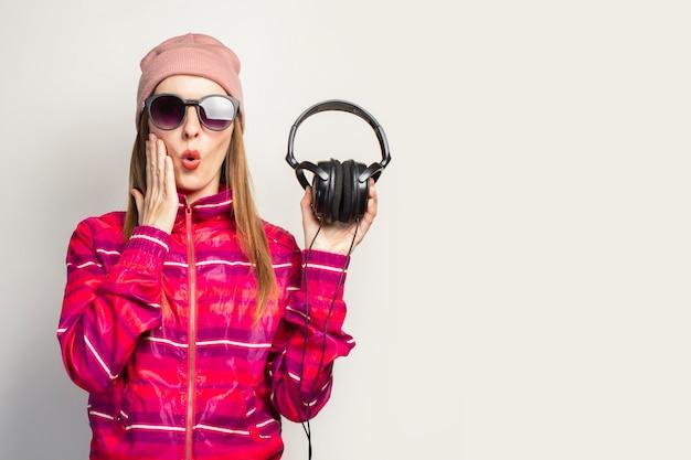 Дружелюбный, эмоциональный. молодая женщина в очках, шляпе и розовой спортивной куртке держит наушники Premium Фотографии