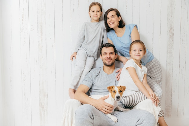 Friendly family pose together against white : two little sisters, father, mother and their pet Premium Photo