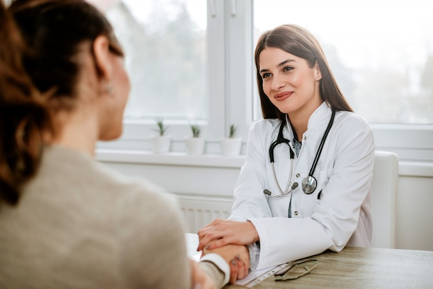 Friendly female doctor holding female patient's hand for encouragement and empathy. Premium Photo