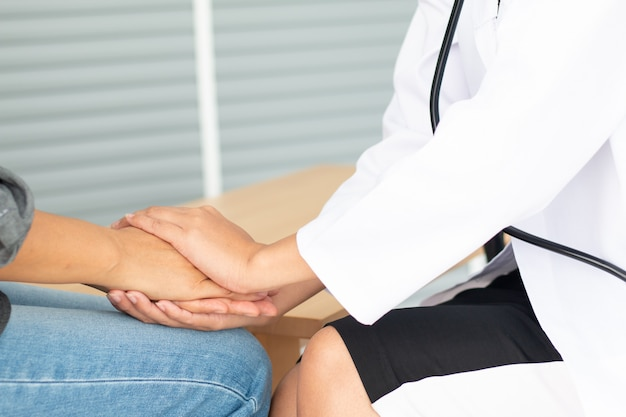 Friendly female doctor's hands holding female patient's hand for encouragement and empathy Premium Photo