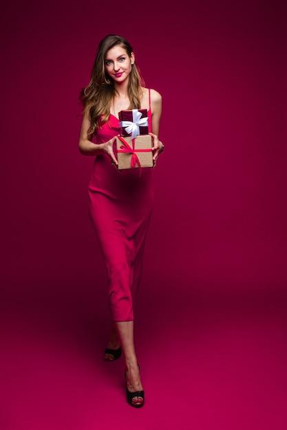 광고 복사 공간 핑크 스튜디오 배경에 포즈 축제 이브닝 드레스를 입고 선물을 가진 친절 맞는 젊은 여자 무료 사진