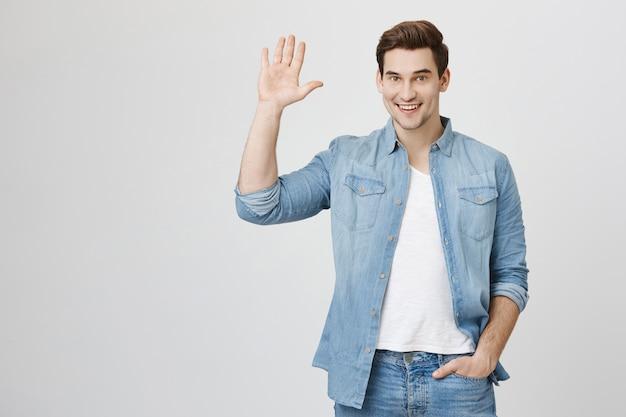 Friendly guy waving hand, saying hello | Free Photo
