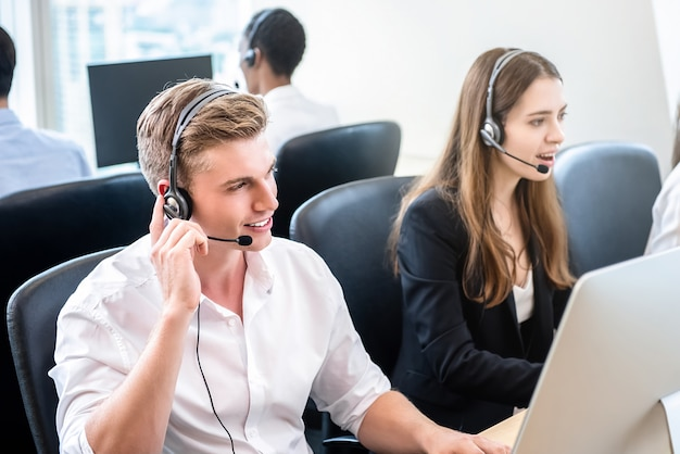 Friendly handsome man working in call center office with team Premium Photo