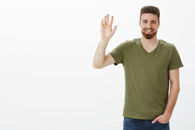 こんにちはまたはこんにちはジェスチャーで上げられた手で恥ずかしがり屋の手を振って、新しい人々との出会いとしてカジュアルにポケットに手を握り、白い壁に挨拶するフレンドリーな外観の魅力的なひげを生やした彼氏 無料写真