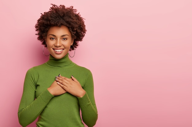 フレンドリーに見える暗い肌の女性は、感謝の気持ちを表し、感謝の気持ちを表し、愛に満ちた心を持ち、両手のひらを胸に保ち、緑のタートルネックを着て、ピンクの背景にポーズをとり、スペースをコピーします 無料写真