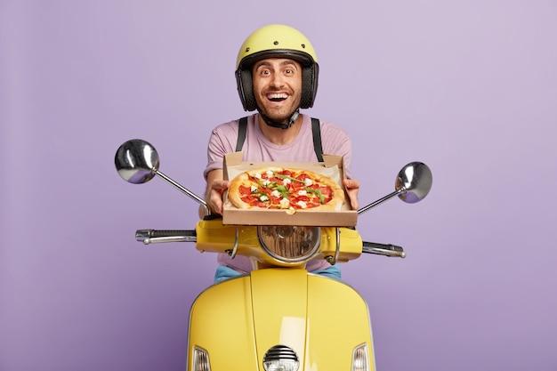 ピザの箱を持って黄色いスクーターを運転しているフレンドリーな見た目の配達員 無料写真
