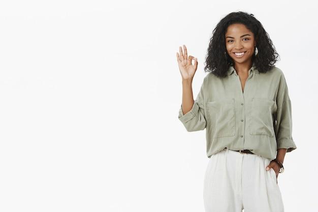 フレンドリーに見える楽しくて自信に満ちたアフリカ系アメリカ人の女性で、巻き毛の髪型は大丈夫です 無料写真