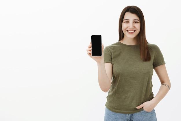 Bruna giovane 20s 20s gioiosa e spensierata dall'aspetto amichevole con il tatuaggio in maglietta verde oliva casual sorridente e ridendo tenero mentre tiene lo smartphone che presenta l'app sullo schermo del telefono cellulare sopra il muro grigio Foto Gratuite