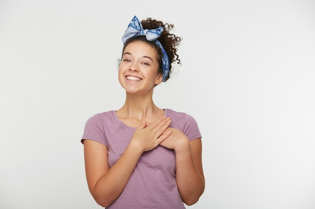 Friendly looking woman with curly hair and headband, keeps hands on chest, hands near heart, looks joyful, cheerfully smiles Free Photo