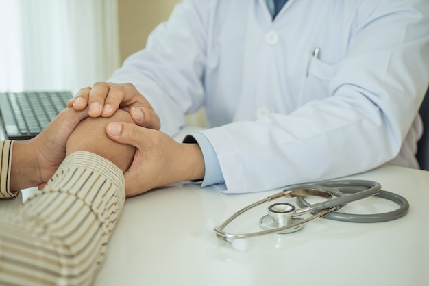 Friendly man doctor hands holding patient hand sitting at the desk for encouragement Premium Photo