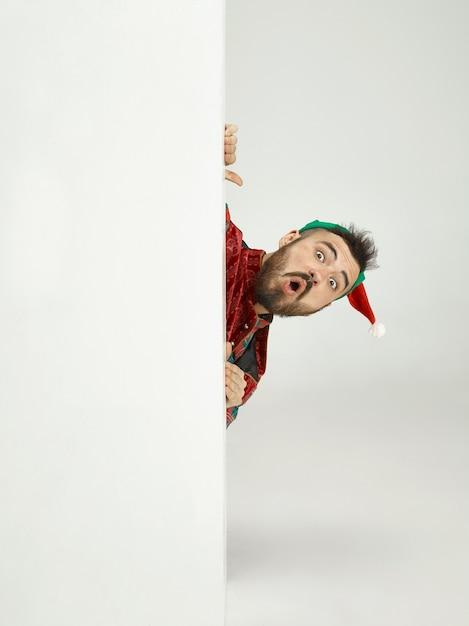 Дружелюбный мужчина, одетый как забавный гном, позирует на изолированном сером Бесплатные Фотографии