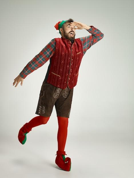Uomo amichevole vestito come uno gnomo divertente in posa su un grigio isolato Foto Gratuite